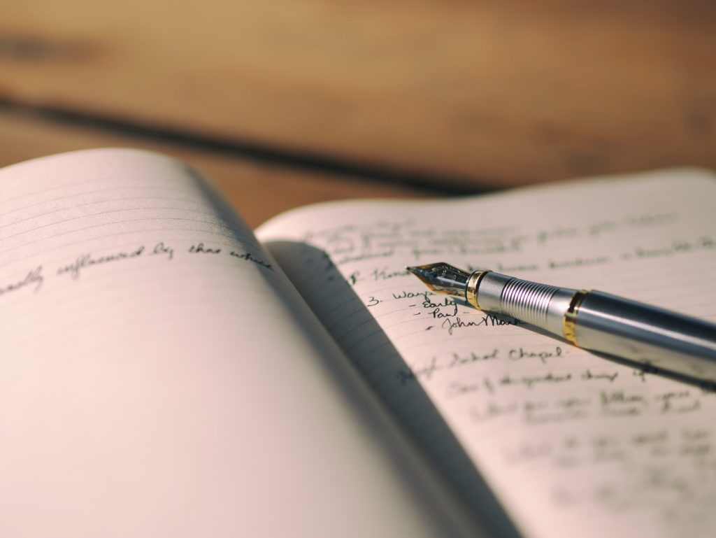 Fountain pen resting on notebook with several entries written in black ink