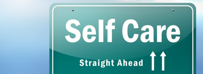Green road sign with white lettering that reads self care straight ahead