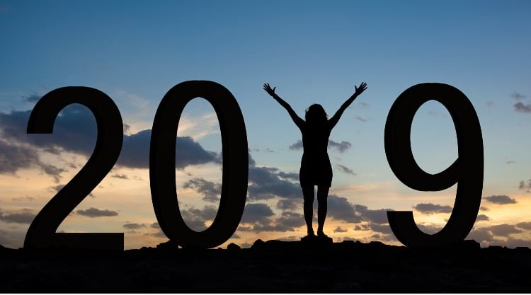 Silhouetted image of the year 2019, with a woman posing as the number 1