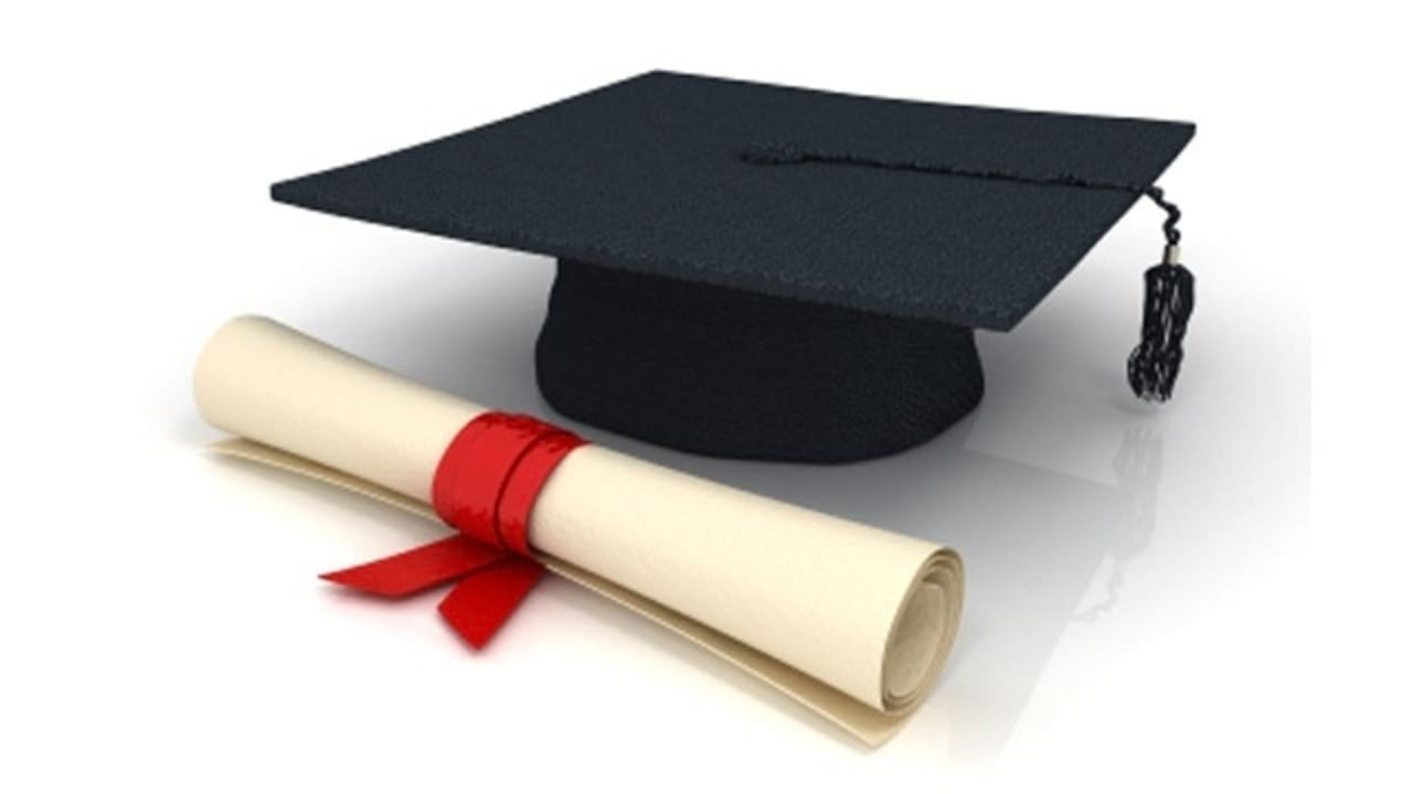 Black graduate cap next to a rolled up diploma