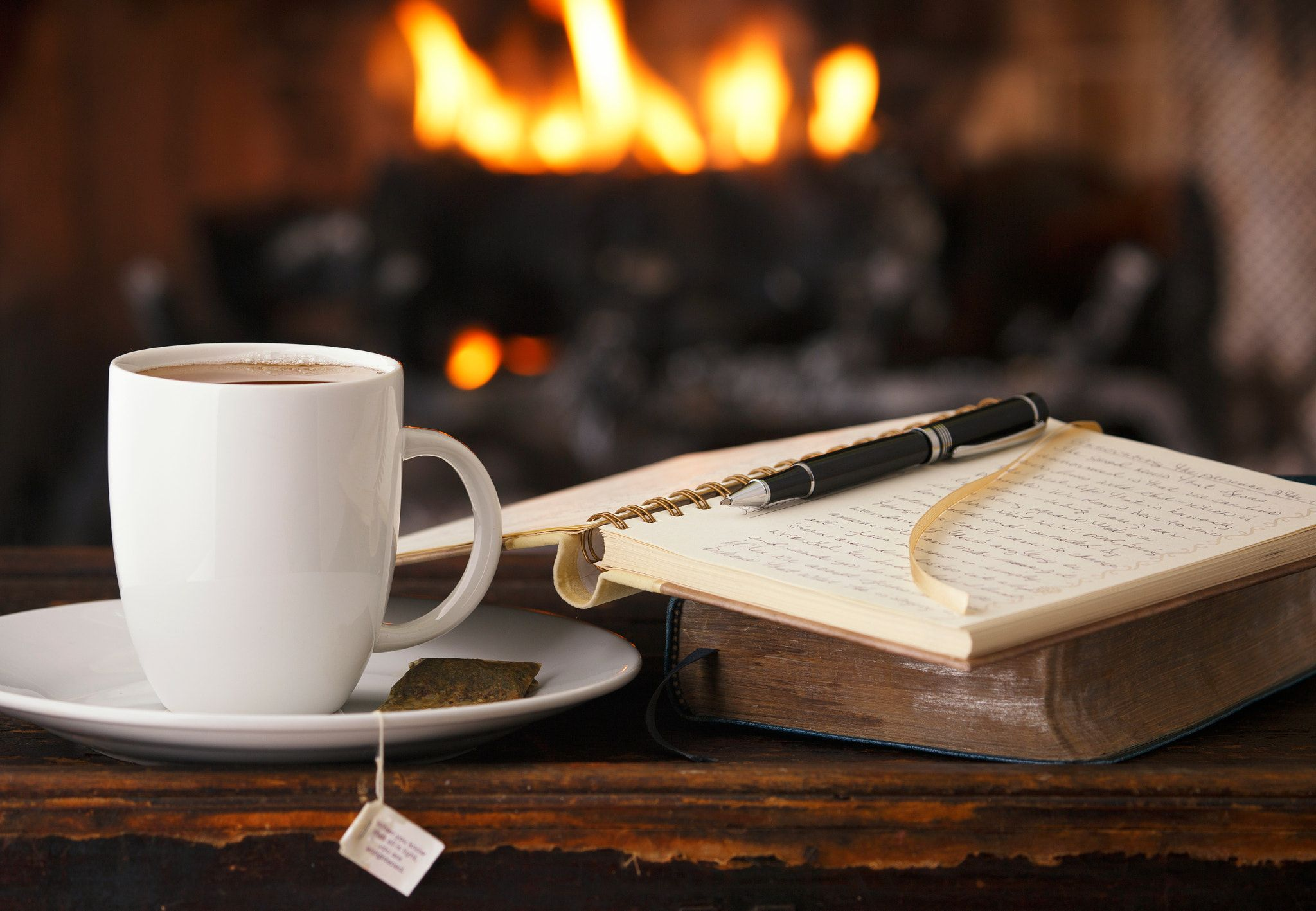 Closeup of a mug of hot chocolate next to an open notebook with a ballpoint pen resting on top, a fireplace burning brightly in the background